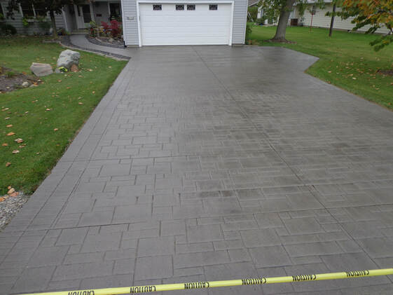 This is a picture of a neatly done concrete driveway repair, Tracy, California